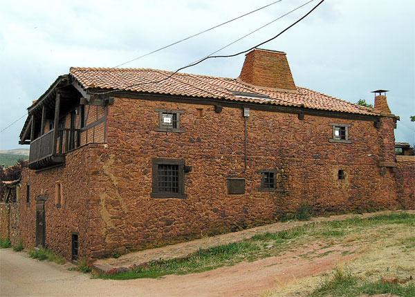Casa típica de los pueblos rojos, como Madriguera / AYTO. RIAZA